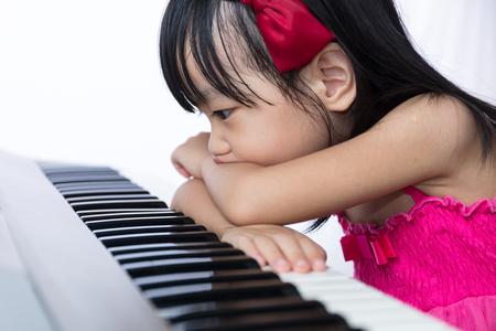 Boring Asian Chinese little girl playing electric piano keyboard in the living room at home.