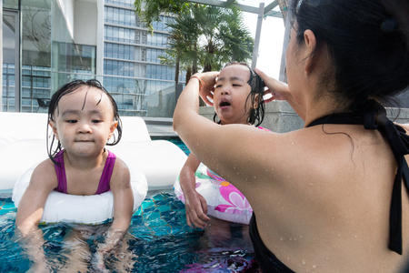 Asian Chinese family playing at the outdoor swimming pool on vacation during summertime. Stock Photo