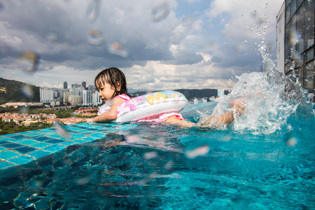 Asian Chinese little girl learning at the outdoor swimming pool in a sunny day.
