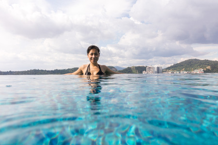 Asian Chinese girl ejoying holiday at outdoor swimming pool with city view Stock Photo