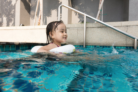 Asian Chinese little girl playing at the outdoor swimming pool during sunny day.