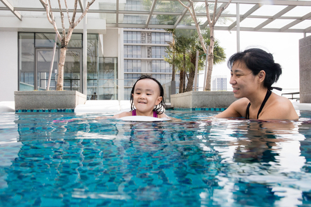 Asian Chinese mother and daugther playing at outdoor swimming pool on sunny day
