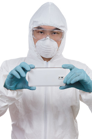 Asian Chinese scientist in protective wear with mobile phone posing for taking photo of evidence in isolated white background. Stock Photo