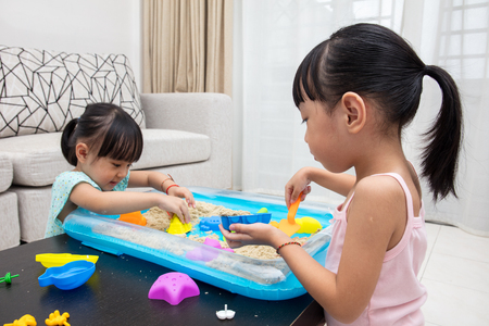 niñas chinas: Happy Asian Chinese little girls playing kinetic sand in the living room at home