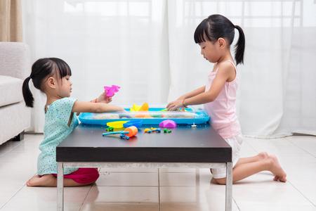 niñas chinas: niñas chinos asiáticos que juegan arena cinética en la sala de estar en casa