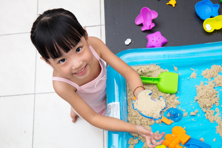 Happy Asian Chinese little girl playing kinetic sand in the living room at home Stock Photo