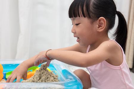 Asian Chinese little girl playing kinetic sand in the living room at home