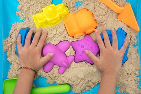 Child's hand close up playing kinetic sand at home indoors. Stock Photo - 74278811