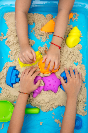 Childs hand close up playing kinetic sand at home indoors. Stock Photo - 74282253