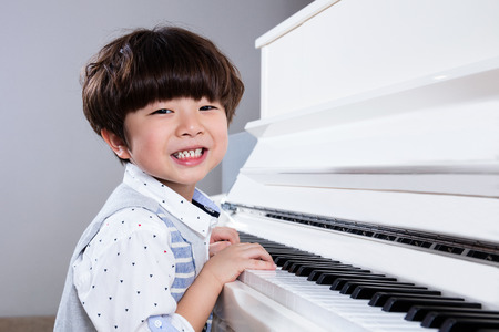 Happy Asian Chinese little boy playing piano in the living room at home.