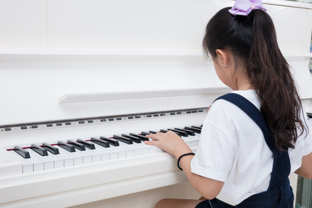 Asian Chinese little girl playing classical piano in the living room at home Stock Photo