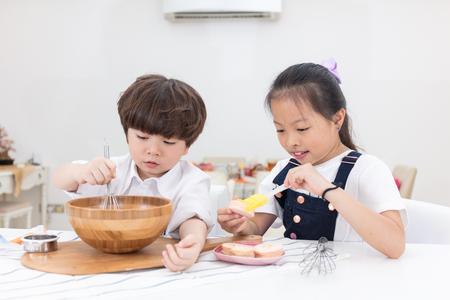 アジア中国弟と妹の自宅のキッチンでクッキーを焼くための準備します。