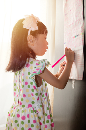 Asian Chinese little girl writing on paper with  back lighting in the living room at home.