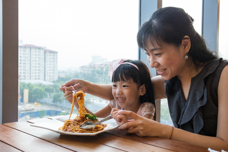 Asian Chinese mother and daughter eating spaghetti bolognese in the restaurant.