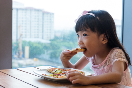 western europe: Asian Chinese little girl eating pizza pepperoni in the restaurant.