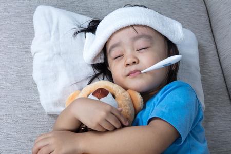 Niña china asiática sosteniendo oso de peluche para la medición de la temperatura de la fiebre Foto de archivo - 74951280