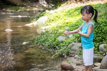 pastime: Asian Chinese little girl angling with fishing rod at the river shore.