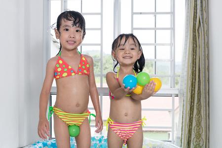 maillot de bain fille: Bonne petite tailleuse chinoise asiatiques s?urs qui jouent dans la piscine gonflable à l'intérieur de la maison.