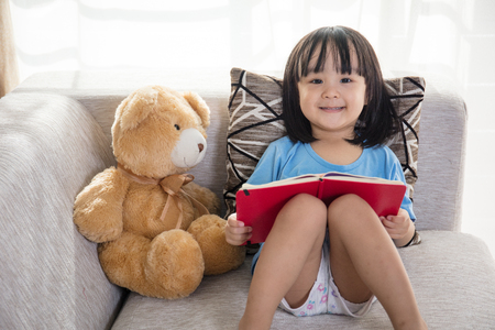 Smiling Asian Chinese little girl reading book with teddy bear on the couch in the living room at home.