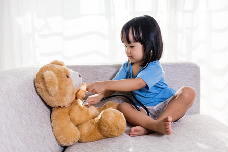 Asian Chinese little girl examination teddy bear with stethoscope in the living room at home. Stock Photo