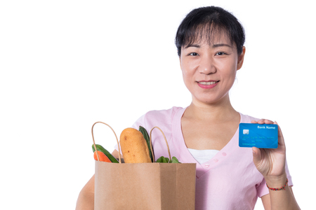 Asian woman holding a shopping bag full of groceries and credit card in hands in isolated White Background