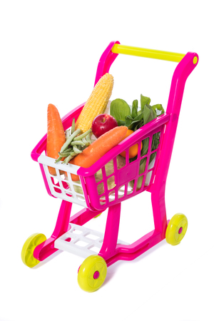 A toy trolley with vegetables in isolated white background.