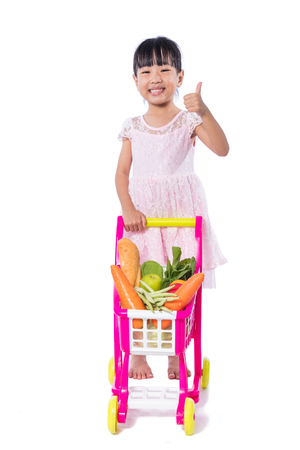 Asian Chinese little girl with shopping trolley full of vegetables in isolated white background.