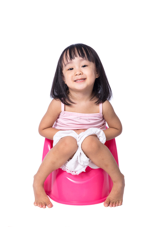 Asian chinese little girl sitting on chamberpot in isolated White Background