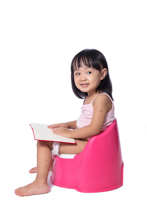 a toilet stool: Asian chinese little girl sitting on chamberpot with book in isolated White Background