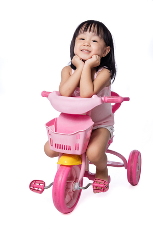 Asian chinese little girl riding a toy tricycle in isolated White Background Stock Photo