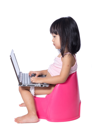 Asian chinese little girl sitting on chamberpot with laptop in isolated White Background