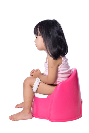 a toilet stool: Asian chinese little girl sitting on chamberpot in isolated White Background