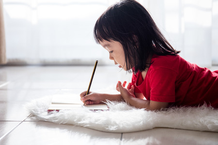 asian children: Asian Chinese little girl lying on the floor drawing in the living room at home