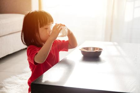 自宅のリビング ルームで牛乳で朝食を持っているアジアの中国少女