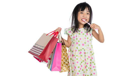 Asian chinese little girl with shopping bags in isolated White Background