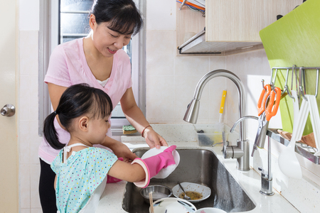 Asian Chinese little girl helping mother washing dishes in the kitchen at home