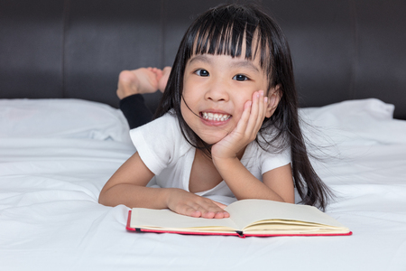 bedtime story: Asian little Chinese girl reading a book on bed in the bedroom Stock Photo
