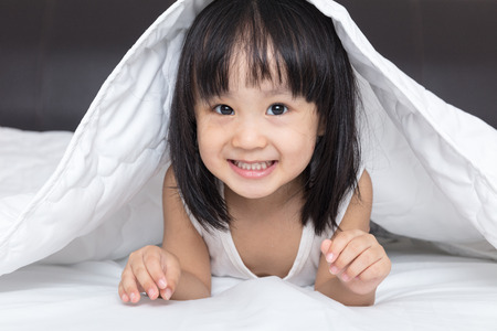 Asian little Chinese girl playing on the bed at home Stock Photo
