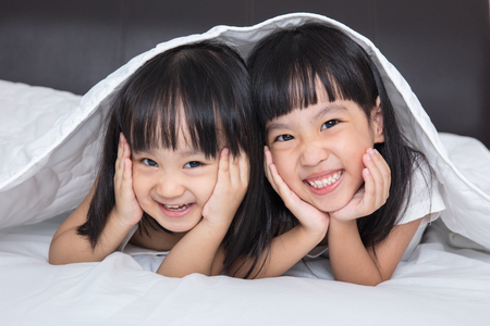 Asian little Chinese girls playing on the bed at home