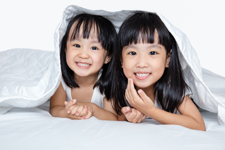 Asian little Chinese girls playing on the bed isolated on white background