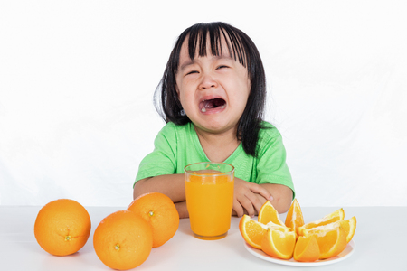 Asian Chinese little girl crying for orange juice in isolated white background