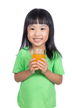 Happy Asian Chinese little girl drinking orange juice in isolated white background