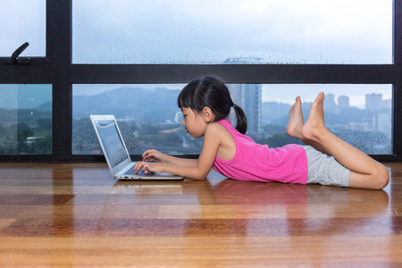 Asian little Chinese girl playing computer at home