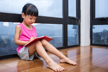 Asian little Chinese girl reading a book near the window at home Zdjęcie Seryjne