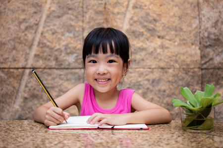 Asian little Chinese girl writing homework at home Stock Photo