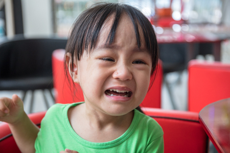 Asian Chinese little girl sitting in chair and crying