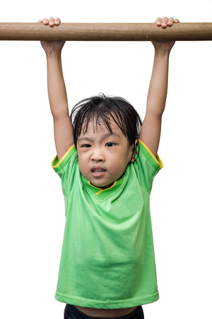 insist: Asian Chinese little girl hanging on horizontal bar in isolated white background Stock Photo
