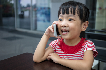 Asian Chinese little girl playing smartphone at outdoor cafe Stock Photo