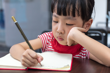 learning by doing: Asian Chinese little girl doing homework at outdoor cafe
