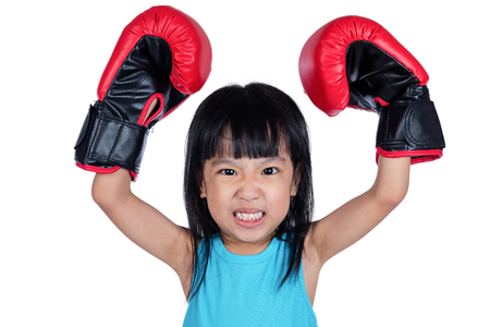 Asian Little Chinese Girl Wearing Boxing Glove With Fierce Expression in isolated white background